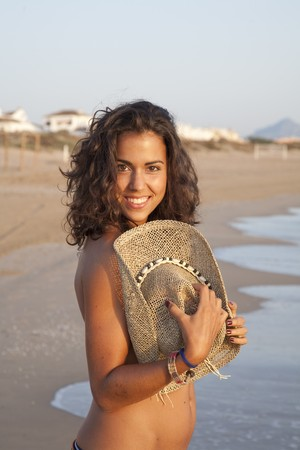 Portrait of young pretty woman with straw hat in her hands, by the beach.