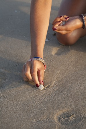 18's: Femenines hands picking up shells on the beach