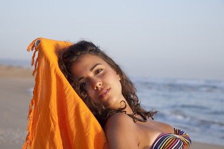 beach wrap: Young pretty woman sunbathing at the beach of Valencia, Spain.