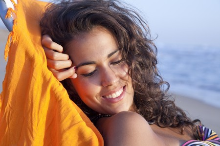 sun bathers: Pretty young latin woman, relaxed sunbathing at the beach. Stock Photo