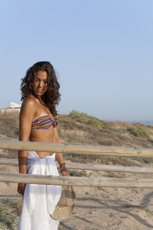 sideway: Young pretty woman by the beach wearing sarong looking sideway.
