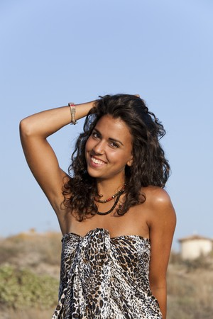 18's: Young pretty woman by the beach wearing sarong looking at camera. Stock Photo