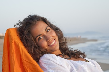 Young pretty woman dressed in white, laying relaxed watching the sunrise by the beach. photo