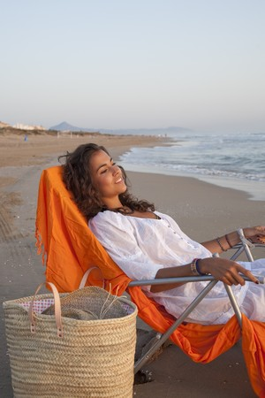 sun bathers: Young pretty woman dressed in white,  laying on sunbed relaxed watching the sunrise by the beach. Stock Photo