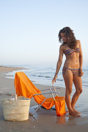 beach wrap: Young pretty woman dressed with stripped bikini,  at the beach of Valencia , Spain.