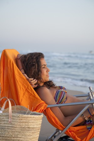 beach wrap: Pretty young latin woman,  sunbathing relaxed at the beach.