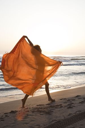 Young pretty woman runing by the beach with orange sarong in her hands. Stock Photo - 8088927