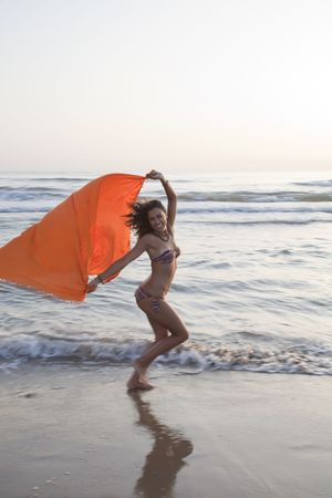 Young pretty woman runing by the beach with orange sarong in her hands. Stock Photo - 8088925