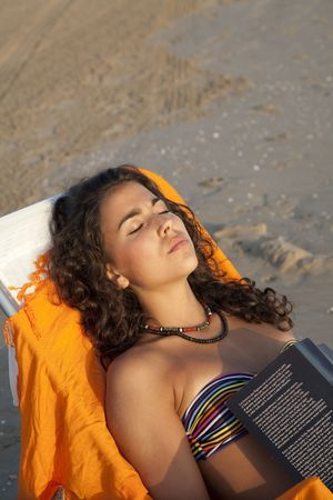 19's: Young pretty woman sunbathing reading a book, at the beach of Valencia , Spain.