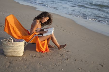 adriana: Young pretty woman sunbathing reading a book, at the beach of Valencia , Spain.