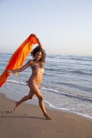 beach wrap: Young pretty woman runing by the beach with orange sarong in her hands.
