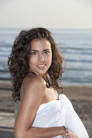 adriana: Young pretty woman wearing white sarong by the beach.