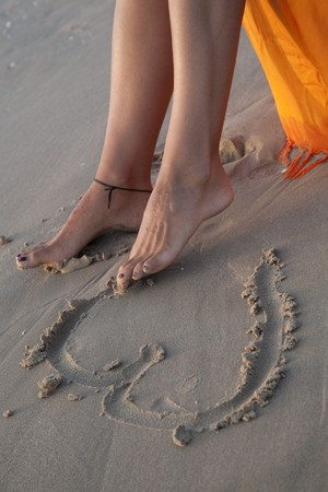 Barefeet drawing a heart in the sand of the beach.