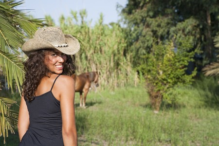 Young latin looking girl at countryside nearby a horse, looking back photo
