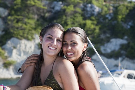 18's: Two young girl friends on boat with wet hair.