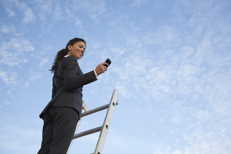 Young latin looking business woman texting with her blackberry up on a ladder with the blue sky inthe backgroudsky. Stock Photo - 8612101
