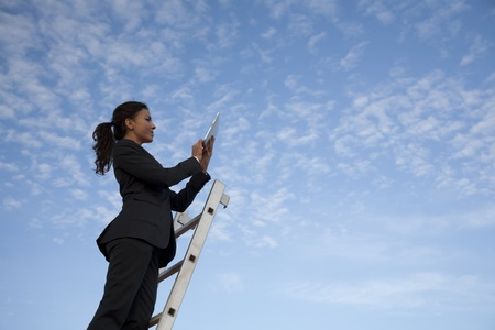 buisiness: Young latin looking business woman, working with her iPad on a roof, with the blue sky in the background. Stock Photo
