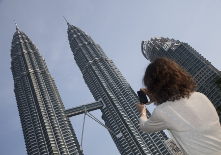 Tourist taking picture of Petronas KL Twin Towers with her mobile phone Kuala Lumpur, Malaysia
