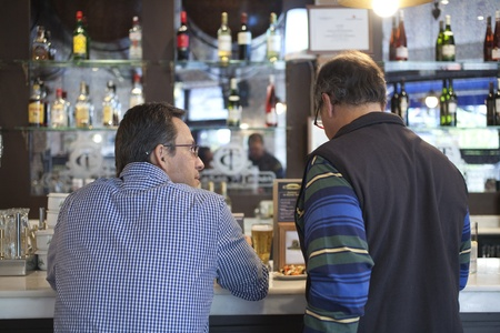 Two adult men talking in a bar, by the  countertop. photo