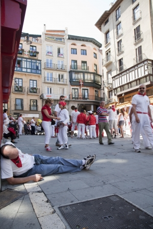 one person with others: Image of drunk man lying on the street in the morning, during San Fermin, Pamplona. People on the street all dressed in white and red.