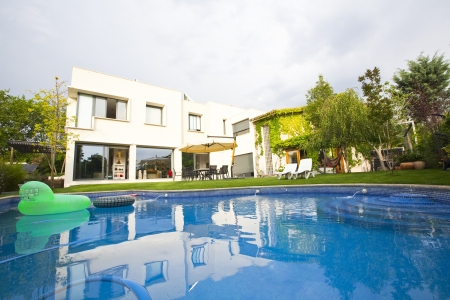 Partial front view of semidetached house from the garden and swimming pool. Stock Photo