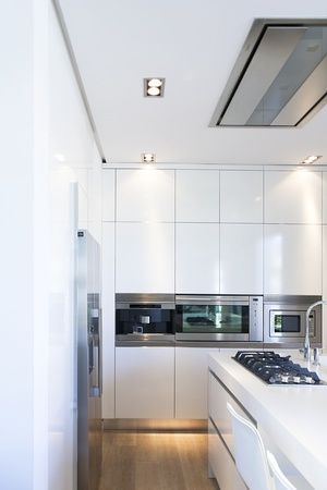 Partial view of modern white kitchen decorated in white with large double door fridge and home appliances of stainless steel.