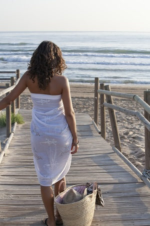 handrails: Young pretty woman wearing white sarong walking to the beach.