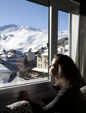 Young girl looking through the window to the  Sierra Nevada Ski Resort, Granada. Stock Photo - 9371767
