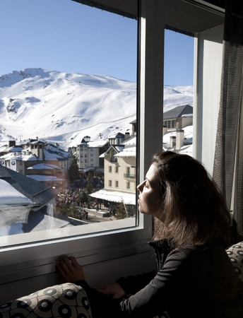 sierra nevada mountains: Young girl looking through the window to the  Sierra Nevada Ski Resort, Granada. LANG_EVOIMAGES