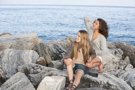 Portrait of young girls on rocks of breakwater at Puerto Banus, Marbella, Spain. photo