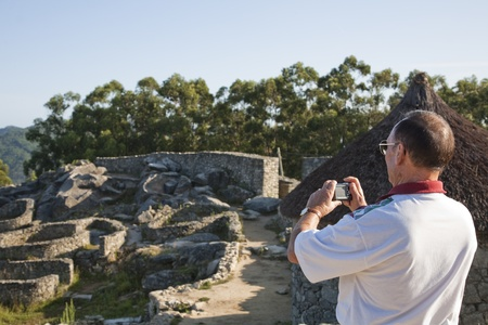 conserved: July 2009. Tourist taking pictures of Castro de Santa Tecla, best conserved Celtic ruins in Spain, La Guardia, Galicia, Spain. Editorial