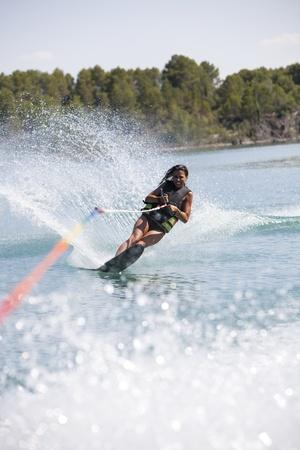 Teenager girl water skiing in lake. photo