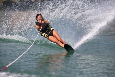 Teenager girl water skiing in lake.