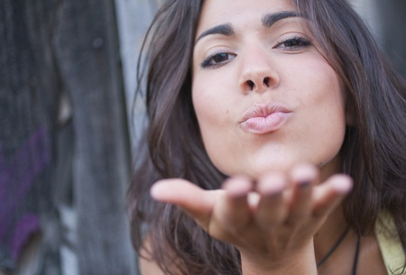 18's: Portrait of young latin woman blowing a kiss. LANG_EVOIMAGES