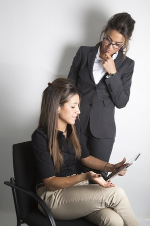 Two young pretty female business executives talking and looking at portable tablet pc Stock Photo - 9638603