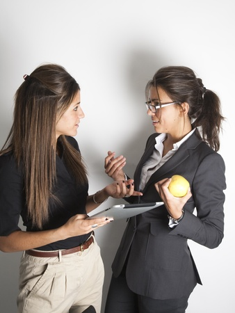 Two young pretty female business executives talking and looking at portable tablet pc Stock Photo - 9638592