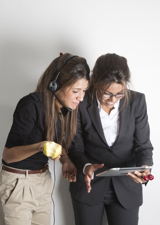 Young two pretty female business executives consulting nervous the portable tablet pc while eating an apple. Stock Photo - 9638593