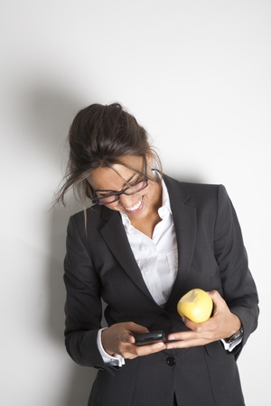 Young pretty female business executive happy reading a message on her smartphone while holding an apple. Stock Photo - 9638596