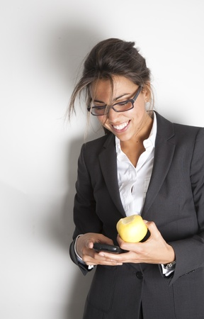 Young pretty female business executive happy reading a message on her smartphone while holding an apple. Stock Photo - 9638599