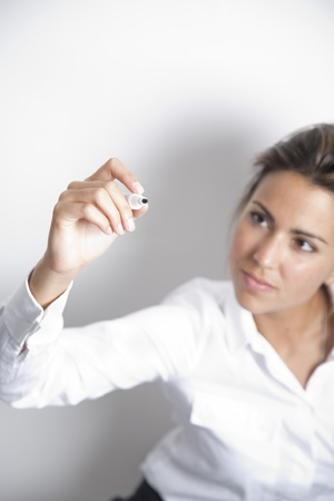 Young female executive with marker on her hand drawing on transparent blackboard. Stock Photo - 9638590