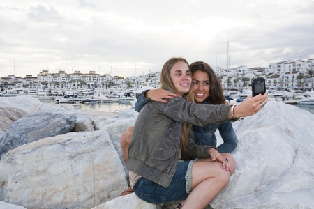 embraced: Two young girl friends at the docks of Puerto Banus, Marbella, Malaga, Spain.