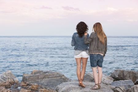 short shorts: Two young girl friends on the rocks of breakwater at Puerto Banus, Marbella, Malaga, Spain.