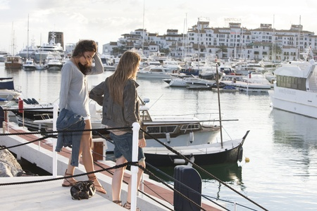 Two young girl friends at the docks of Puerto Banus, Marbella, Malaga, Spain. Stock Photo - 9638608