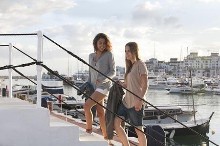 Two young girl friends at the docks of Puerto Banus, Marbella, Malaga, Spain. photo