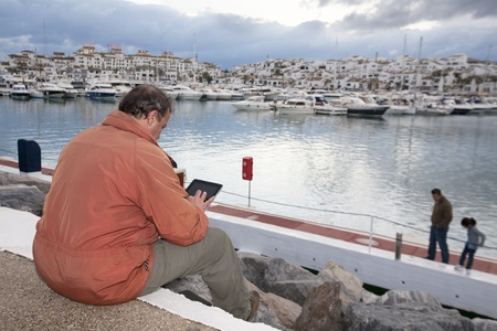 Adult man with his portable tablet pc at harbour of Puerto Banus, Marbella, Spain. Stock Photo - 9638613