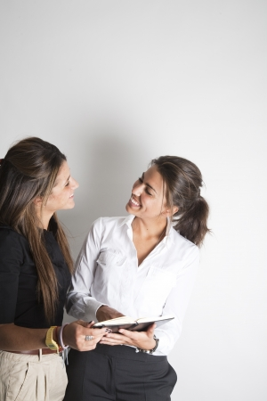 Two young pretty female business executives talking and looking at book photo