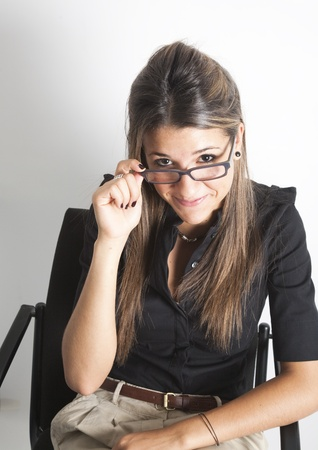 Portrait of young pretty female executive, wearing glasses, with black shirt smiling at camera. photo