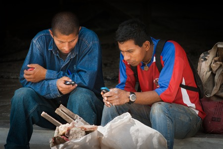 Mindo, Ecuador  August 3, 2011 - Two workers are messaging with their mobile phones waiting for the bus to come back home