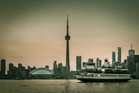 imply: Skyline of Toronto with the Toronto Islands Ferry. Blurred ferry to imply motion. Green toned.