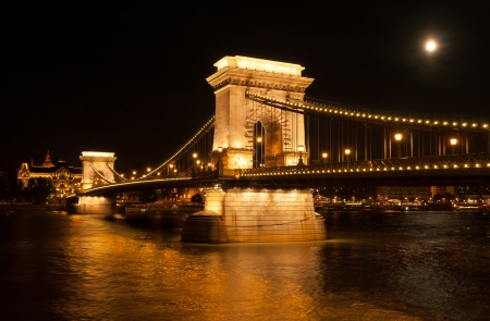 chain bridge: The Chain Bridge with the Gresham Palace and Danube river in Budapest at full moon - Hungary at night